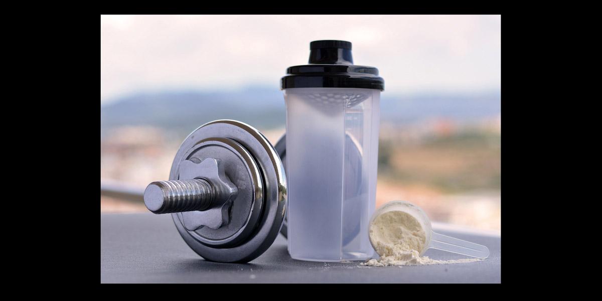 Bebida de suplemento proteico junto a equipos de ejercicio